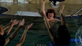 Zatímco Uršula mává plavkami nad hlavou, cosi plave těsně pod hladinou.