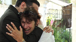 Zdrcená matka Janis objímá přítele své zesnulé dcery Rega Travisse.