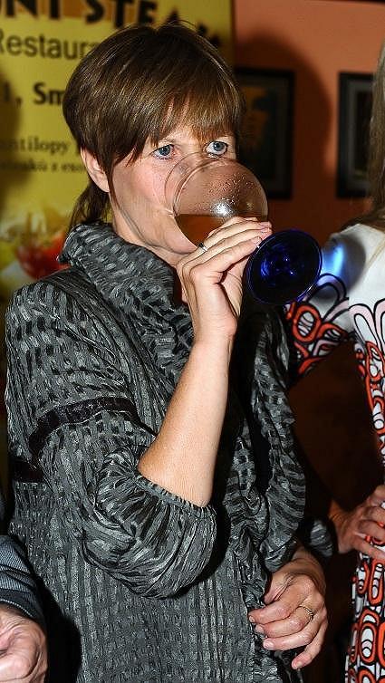 Jitka ochutnává své víno.