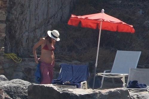 Carla Bruni pod slunečníkem na pláži.