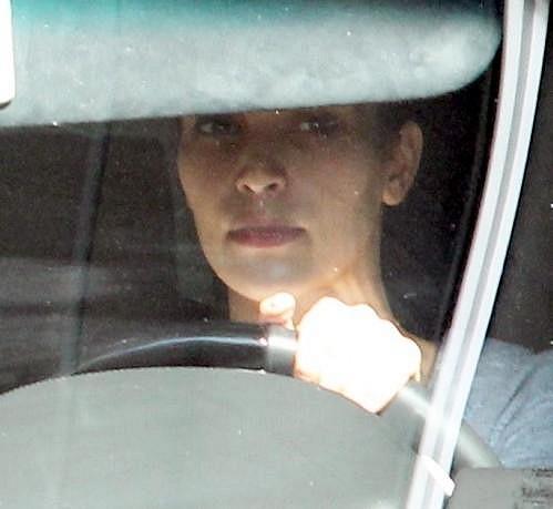Nenalíčená Kim za volantem svého vozu.