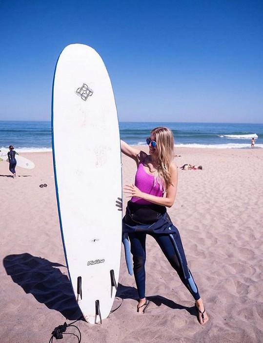 Modelka se na dovolené učí surfovat.