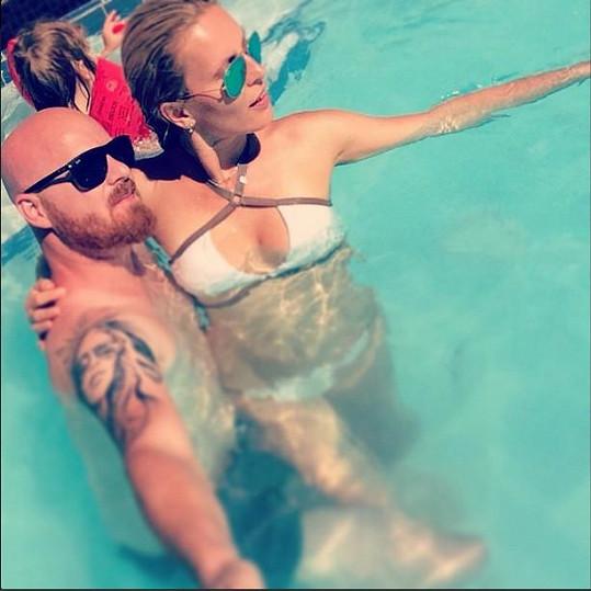 Modelka s manželem dovádí v bazénu.