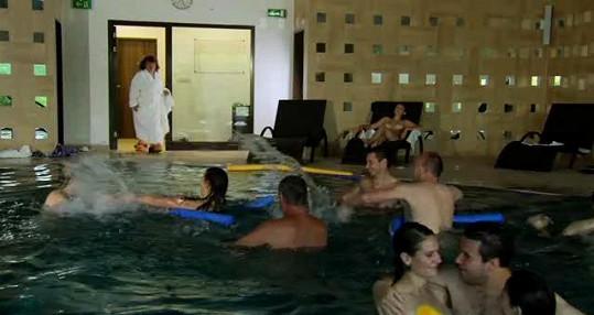 Uršula přichází k bazénu plnému nahých lidí.