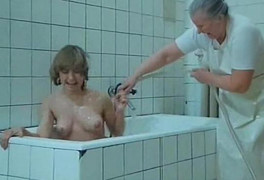 Veronika Žilková rezignovaně klečí a snáší mytí ledovou vodou.