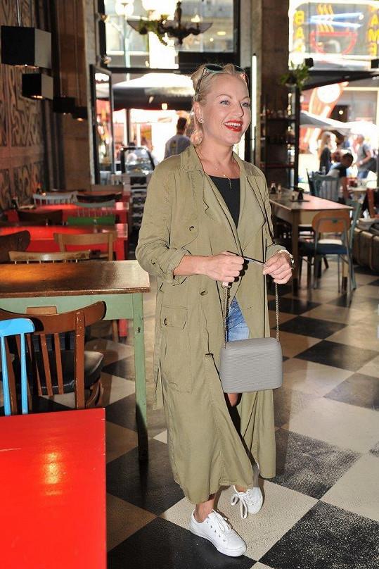 Martina Pártlová trendy celek, tvořený džínovými mikro šortkami, topem a vzdušným kabátem, doplnila nenápadnými teniskami a kabelkou na řetízku.