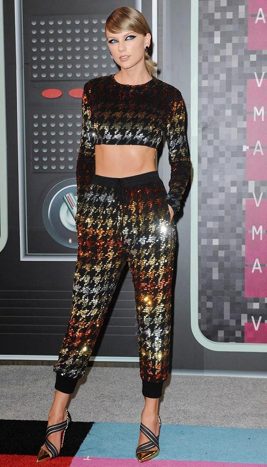 Sáhla po kalhotách a tím razantně vynikla. Miláček Ameriky Taylor Swift doslova zářila v kalhotovém kompletu od Ashish, který byl tvořen materiálem s odlesky s kohoutí stopou. Celek doplnila střevíci Pumpstagram od Christiana Louboutina a vše doladila ulíznutým vlasovým stylingem a kočičím líčením.