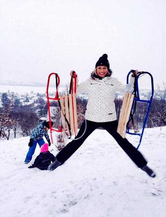 Lucie Borhyová si s dětmi (v pozadí) užívá sněhovou nadílku.