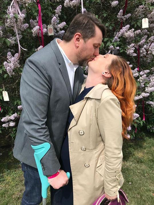 Moderátor políbil manželku pod rozkvetlým stromem.