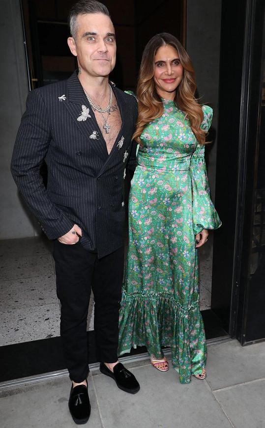 Za staronovým účesem Robbieho Williamse je jeho žena Ayda.