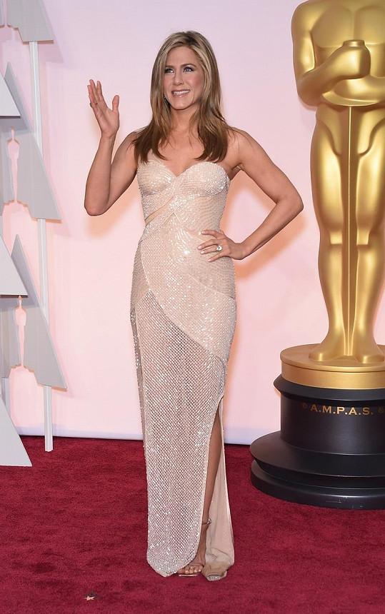 Jennifer Aniston vypadá vždy výborně v barvě těla či pudru. Herečka si je toho vědoma, a proto pro tuto významnou příležitost zvolila dramaticky řešený model z ateliéru Versace bez ramínek.