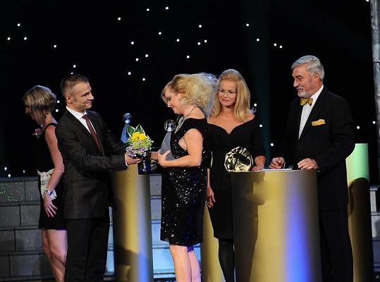 Iveta s moderátory Janem Rosákem a Jitkou Asterovou přebírá cenu od Janise Sidovského.