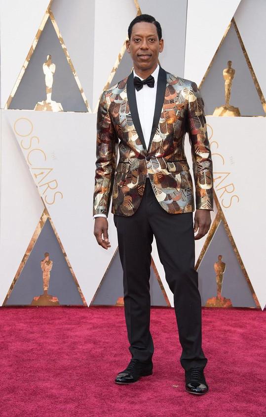 Nemůžeme se ubránit pocitu, že toto metalické smokinkové sako se stříbrnými a bronzovými motivy bude možná neprůstřelné. Orlandu Jonesovi zároveň vůbec nesedí příliš široké a dlouhé nohavice.