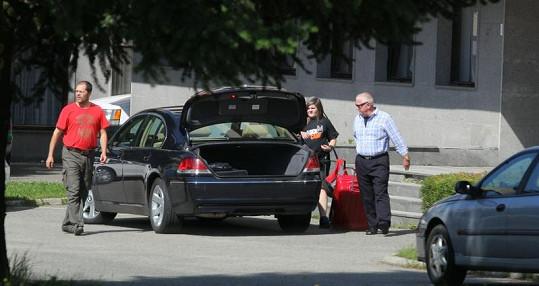 Řidič nese Arturův kufr do auta.