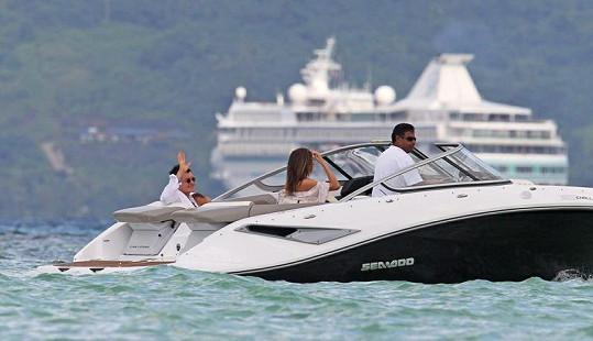 Rodinka na projížďce na motorovém člunu. V pozadí s velkou výletní lodí.