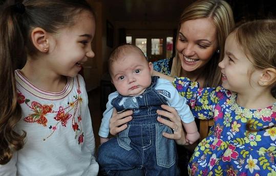 Spokojená maminka drží Harrisona, vlevo pětiletá Ella, vpravo tříletá Evie.