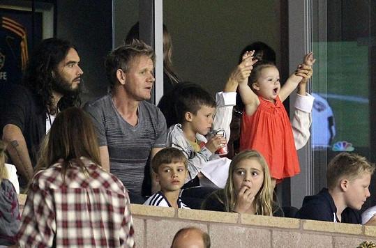 Takhle roztomilá Harper fandila tatínkovi. Po straně sedí Gordon Ramsay a Russell Brand.