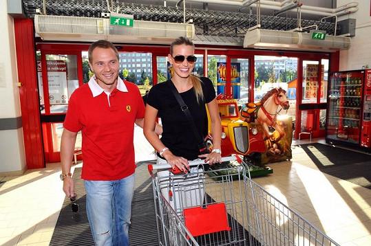 Kristýna Lebedová a Milan Richter vjíždějí s prázdným košíkem do supermarketu.