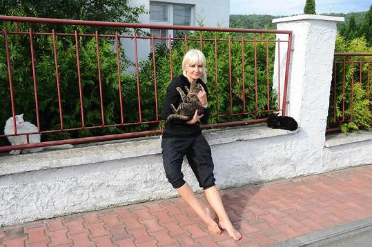 Bára s kočkami před plotem svého domu.