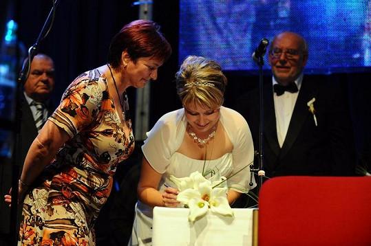 Pavlínka Nedvědová za dohledu matrikářky stvrzuje sňatek podpisem.