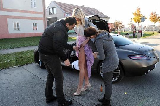 Fotograf s asistentkou upravují šaty.