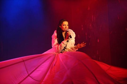 Těla tanečníků pokrytá látkou vynesla Olgu nad zem a vytvořila jí obrovskou sukni.