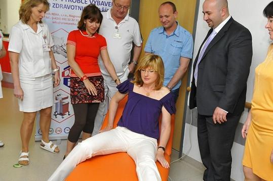 Štěpánka Duchková si za pomoci Michaely Dolinové, Davida Novotného a sponzora Radka Jakubského zkouší polohovatelné lehátko.