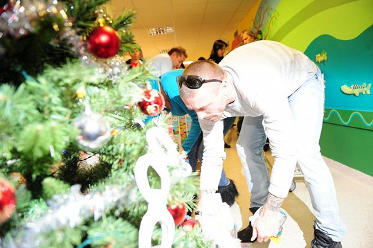 Tomáš Řepka ukládá pod stromeček vánoční dárky.