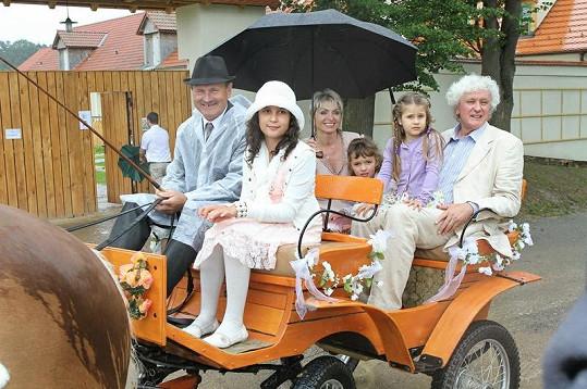 Novomanželé v kočáře s dětmi z příbuzenstva.