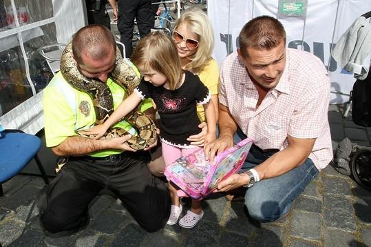 Petr a Romana Jáklovi sledují, jak jejich dcerka Sofinka hladí hada.