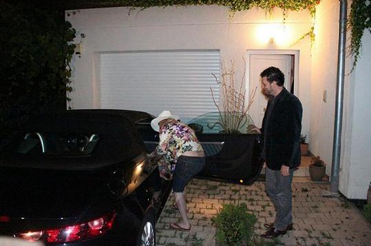 Domenico láskyplně kouká, jak jeho milá nastupuje do auta.