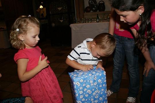 Malý Daniel zkoumavě rozbaluje dárek od manželů Gottových. Přihlíží jejich dcera Nelly Sofie a neteř nevěsty Eliška.