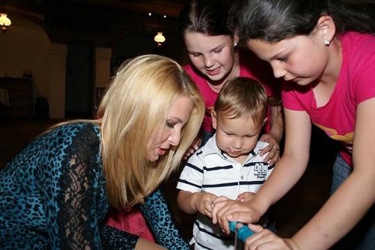Ivana Gottová dává malému Dandovi nezbytnou instruktáž před první jízdou. Přihlížejí neteře Ilony Natálka a Eliška.