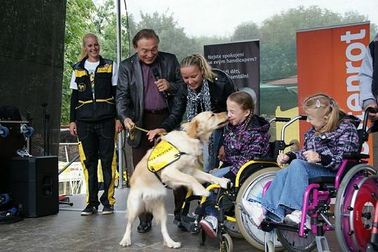 Karel předává asistenčního psa postiženým trojčatům rodiny Kubíkových.