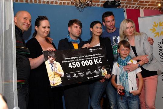 Kmotři s Norbertem Petickým (třetí zleva) předávají šek.