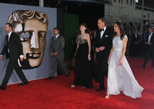 Královská dvojice u sochy divadelní masky představující ceny BAFTA.