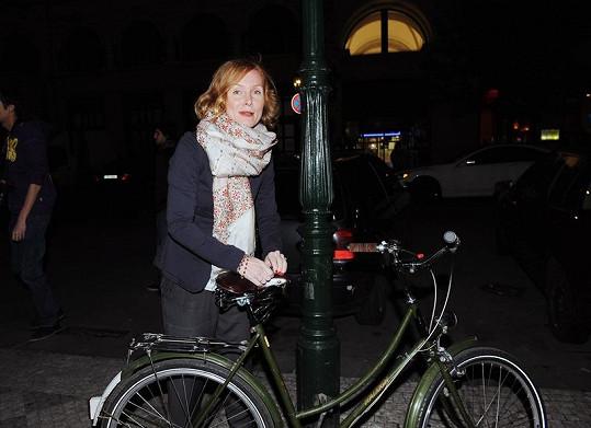 Petra přivazuje své kolo k lampě před barem v Rytířské ulici.