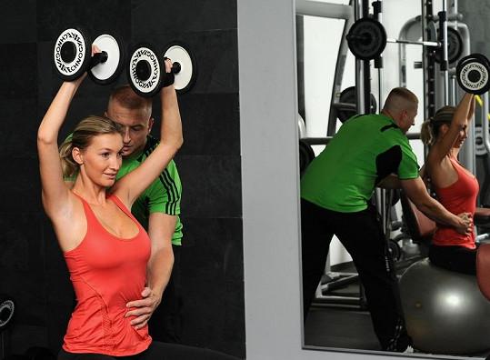 Při cvičení jí pomáhá trenér Tomáš Hreško.