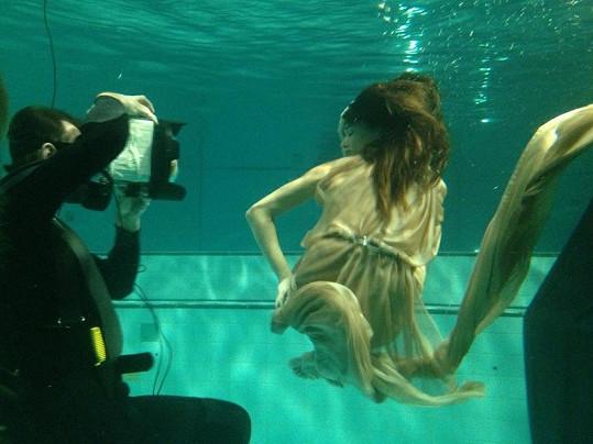 Fotograf v potápěčském obleku s modelkou v bazénu.