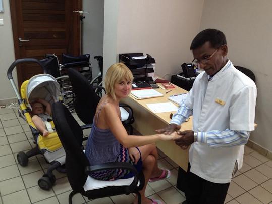 Hotelový doktor ošetřuje Lucce poraněnou ruku.