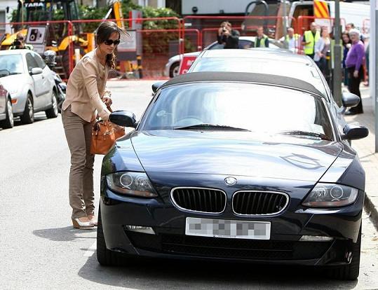 Pohledná brunetka u svého auta.