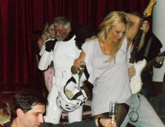 Rozjetá Pamela Anderson trsá se skleničkou v ruce.
