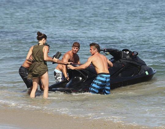 Sean Penn a dva další muži pomáhali pohledné brunetce nasednout na vodní skútr.