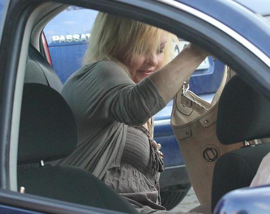 Zpěvačka nasedá do auta bodyguardů.