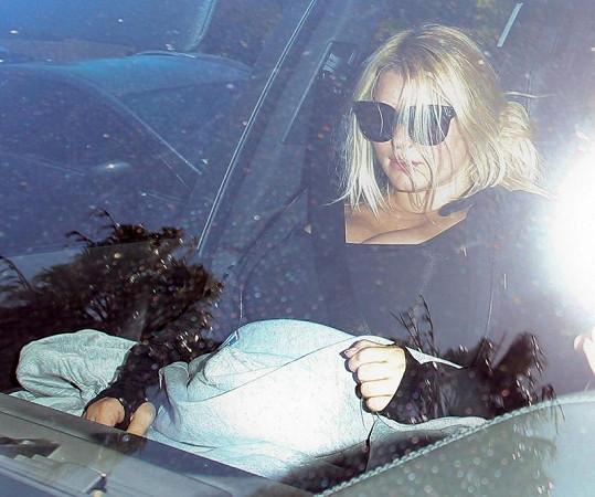 Zpěvačka seděla v autě a tvářila se nepřítomně.
