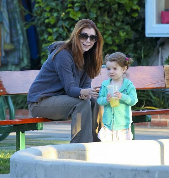 Hannigan s dcerkou na pískovišti.