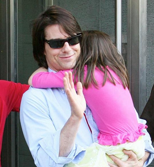 Přestože Tom Cruise musel uklidňovat svou dceru, stačil na paparazzi i zamávat.