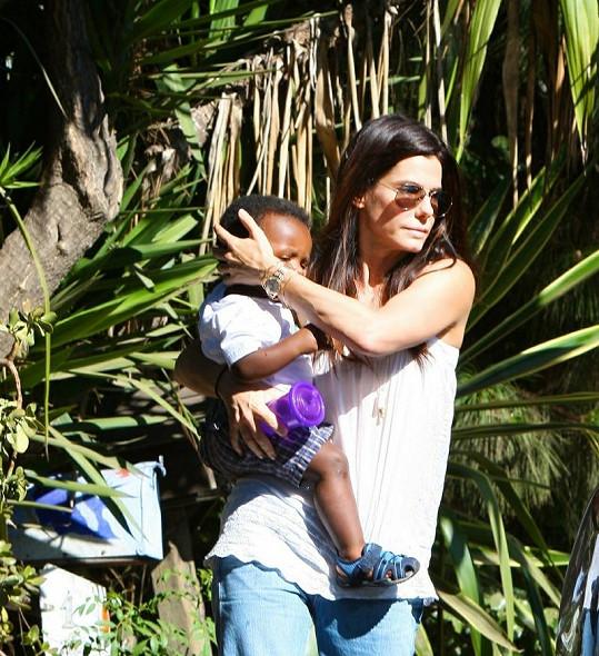 Sandra Bullock se synem Louisem odchází z návštěvy u přátel.