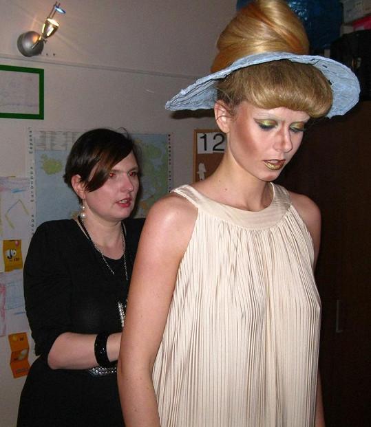 Návrhářka pomáhá oblékat modelku.