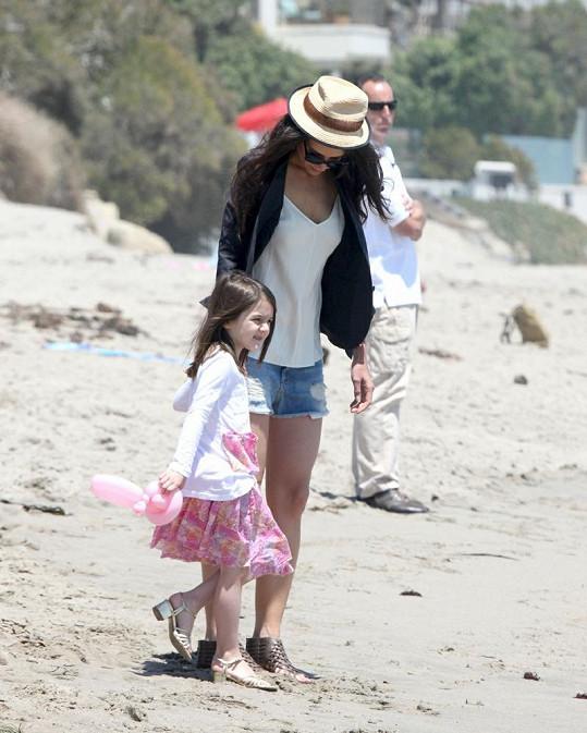 Katie s každým krokem zapadla podpatky do písku.